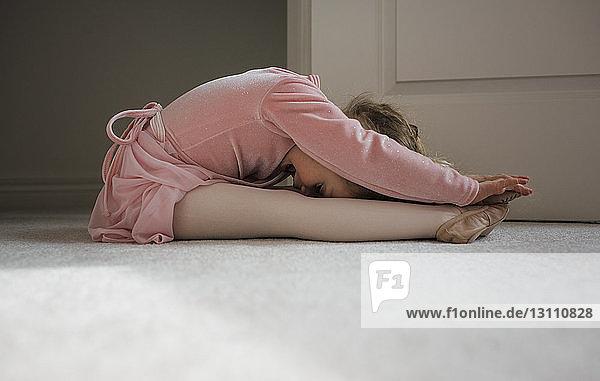 Seitenansicht eines Mädchens in Ballettkostüm  das zu Hause auf dem Boden tanzt