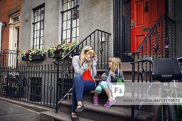 Verspielte Mutter hält Kekse vor die Augen  während sie mit der Tochter auf den Stufen sitzt