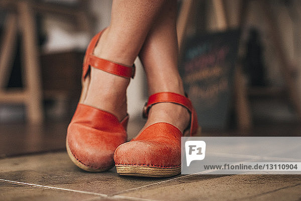 Low section of artist wearing sandals at home