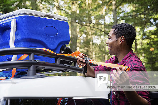 Happy man tying cooler on roofrack of car during vacation