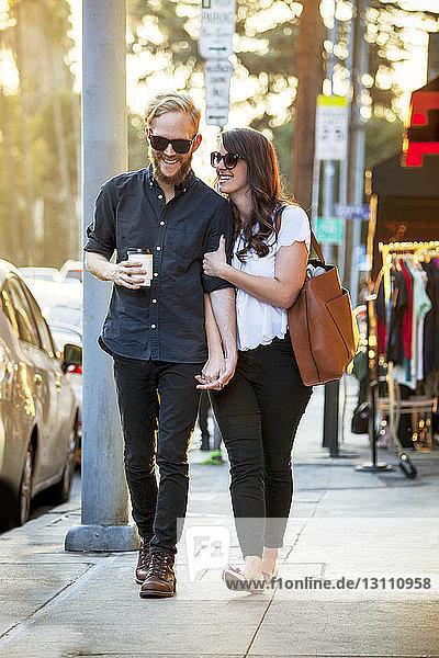 Glückliches Paar beim Gehen auf dem Bürgersteig