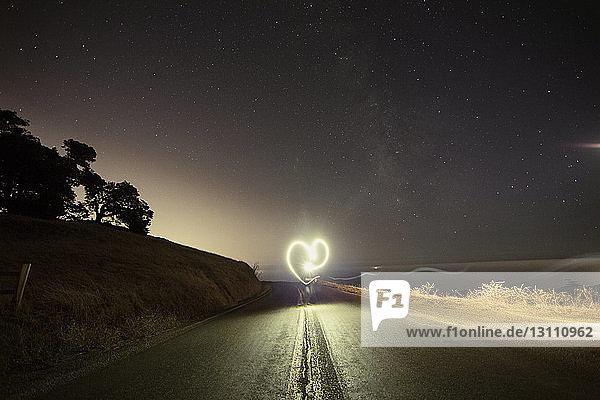 Person macht Herzform,  während sie nachts auf einer Bergstraße Lichtmalerei ausführt