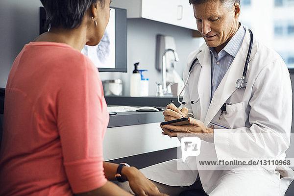 Männlicher Arzt schreibt im Notizblock  während er mit der Patientin in der Klinik sitzt Männlicher Arzt schreibt im Notizblock, während er mit der Patientin in der Klinik sitzt