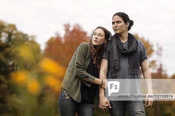 Paar,  das sich beim Gehen auf dem Feld an den Händen hält und wegschaut