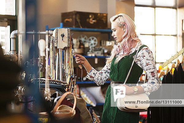 Junge Frau schaut auf Halskette im Laden
