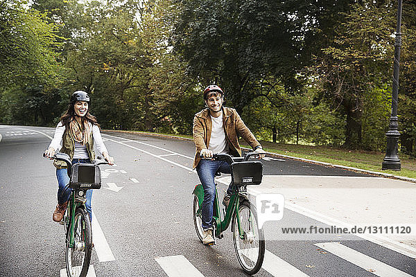 Cheerful couple riding bicycle on road at park