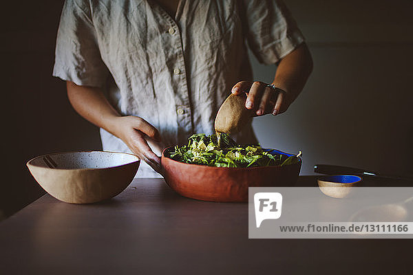 Midsection of woman adding oil to avocado and spinach salad at home