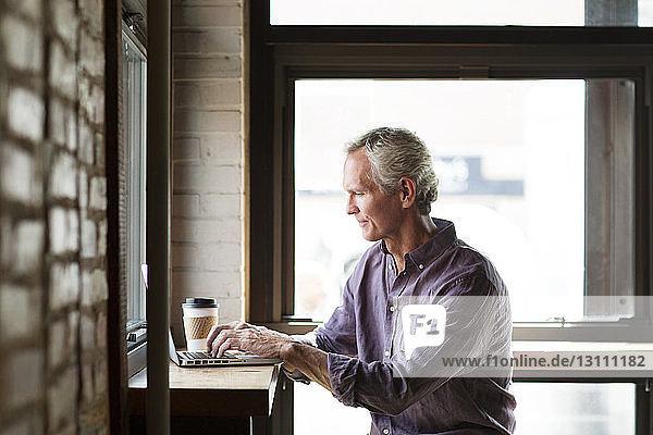 Reifer Mann mit Laptop am Tisch  der im Café an Glasfenstern sitzt