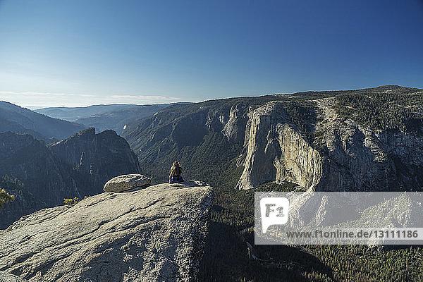 Frau sitzt auf einer Klippe im Yosemite-Nationalpark vor blauem Himmel