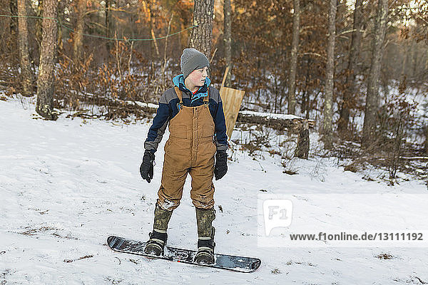 Boy snowboarding on snow covered field in forest