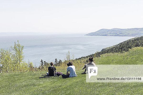 Hochwinkelansicht von Geschwistern  die auf einem Hügel gegen das Meer sitzen