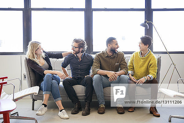Happy business people talking while sitting on sofa in office