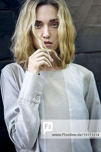 Porträt einer selbstbewussten jungen Frau mit blonden Haaren an der Wand stehend