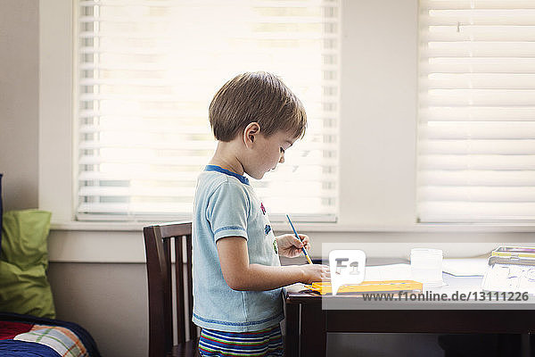 Boy writing in book on table