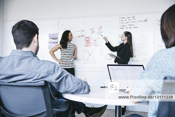 Geschäftsfrau erklärt den Kollegen bei einer Besprechung im Büro