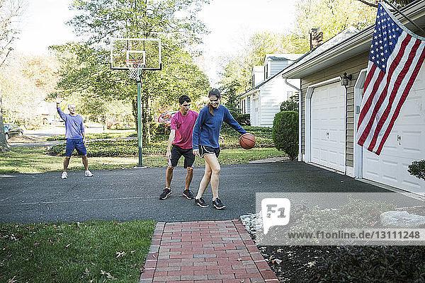 Glückliche Familie spielt Basketball im Hinterhof