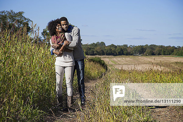 Couple embracing on grassy field against blue sky