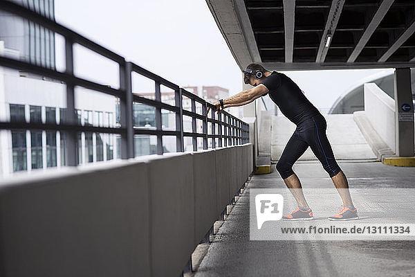 Seitenansicht eines müden männlichen Athleten  der sich auf dem Parkplatz an ein Geländer lehnt