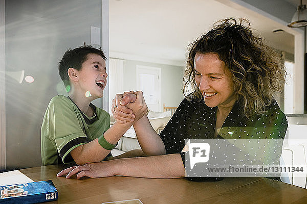 Playful mother arm wrestling with son on table at home