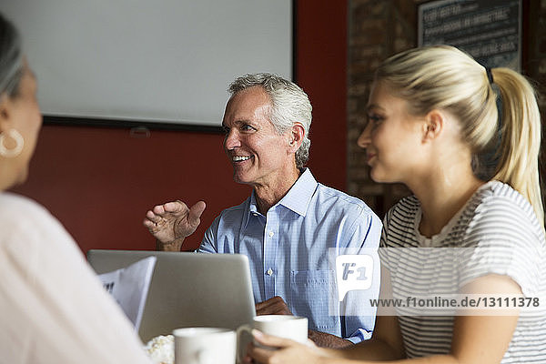 Smiling businessman talking to colleagues during meeting at cafe