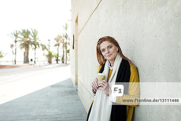 Porträt einer reifen Frau mit Einwegbecher  die in der Stadt an der Wand steht