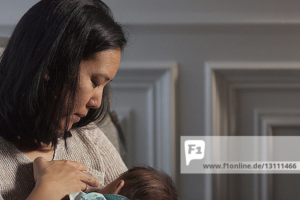 Close-up of mother breastfeeding daughter while sitting at home