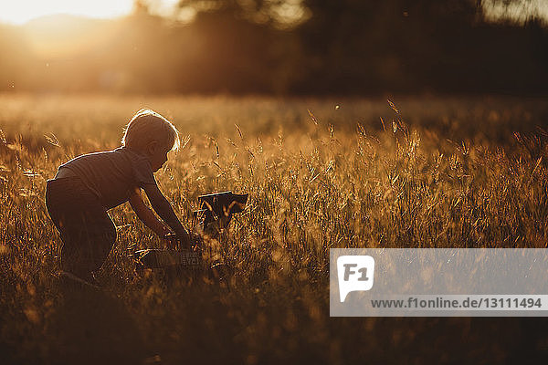 Side view of boy playing with toy earthmover on field