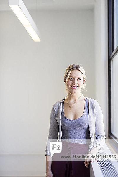 Porträt einer lächelnden Geschäftsfrau,  die in einem neuen Büro am Fenster steht