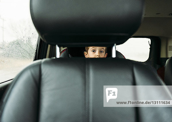 Portrait of boy looking through vehicle seat