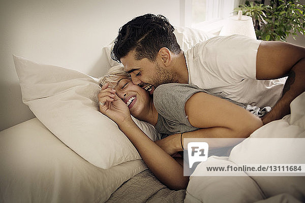 Cheerful young couple lying on bed at home