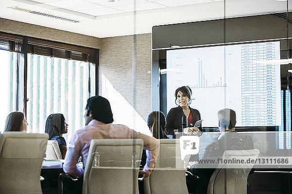 Businesswoman giving presentation in meeting seen through glass window