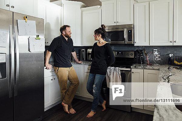 Paar redet  während es zu Hause in der Küche steht