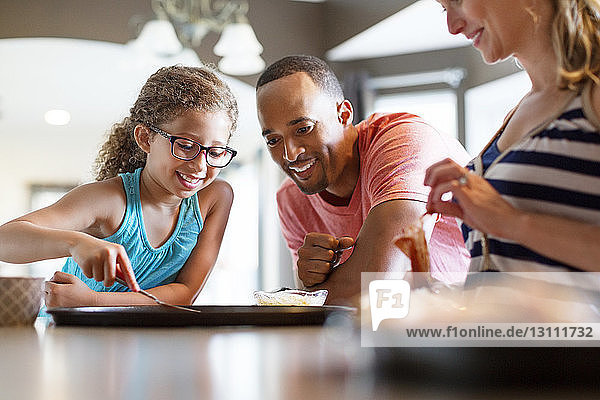Glückliche Familie bereitet zu Hause Pizza zu