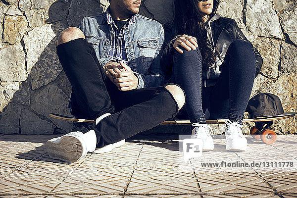 Niedriger Teil des Paares sitzt auf einem Skateboard gegen eine Steinmauer