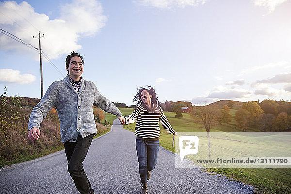 Fröhliches Paar rennt auf Fußweg gegen den Himmel