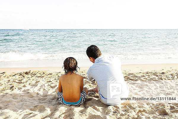 Rear view of father and son sitting on sand at beach