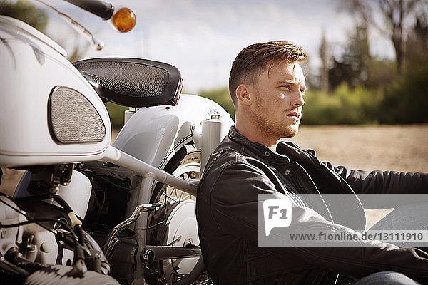 Nachdenklicher Mann lehnt auf Motorrad