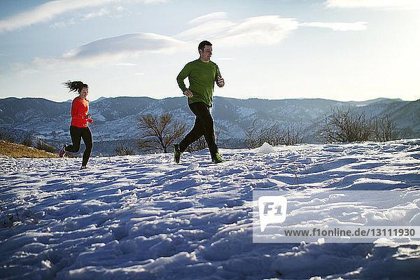 Paar joggt auf Schneefeld gegen den Himmel