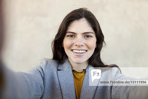 Portrait of cheerful young woman against wall in city