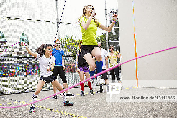 Friends performing double Dutch on street against fence