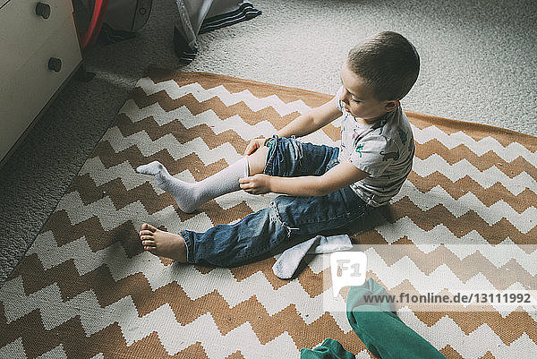 High angle view of boy pulling on sock while sitting on carpet at home