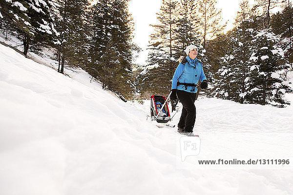 Frau mit Sohn im Schlitten auf verschneitem Feld gegen Bäume