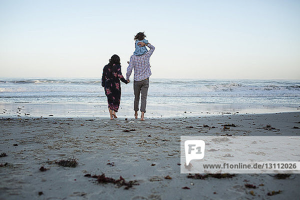 Rear view of man piggybacking daughter while holding woman's hand at beach against clear sky