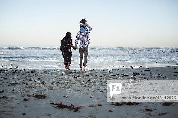 Rückansicht eines Mannes  der seine Tochter huckepack nimmt  während er die Hand einer Frau am Strand gegen den klaren Himmel hält