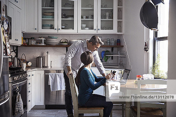 Couple looking at laptop computer in kitchen