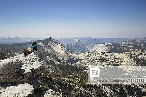 Frau entspannt sich auf Berg vor klarem Himmel und schaut auf Aussicht