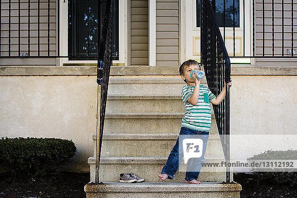 Junge trinkt Wasser  während er auf Stufen steht