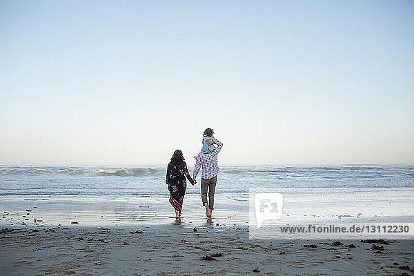 Rückansicht eines Mannes  der seine Tochter huckepack nimmt  während er die Hand einer Frau am Strand vor klarem Himmel an der Küste hält