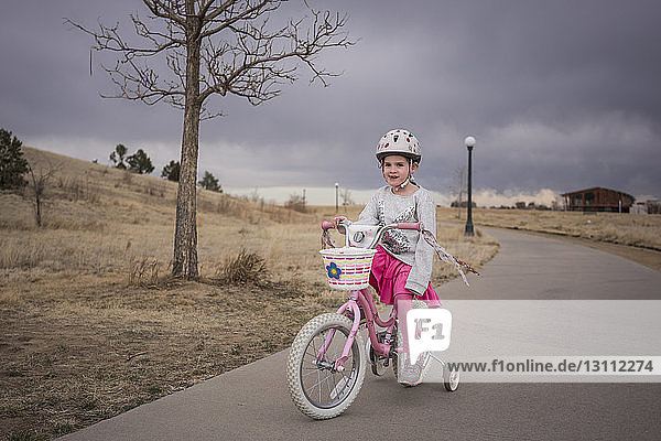 Girl looking away while riding bicycle on road against cloudy sky