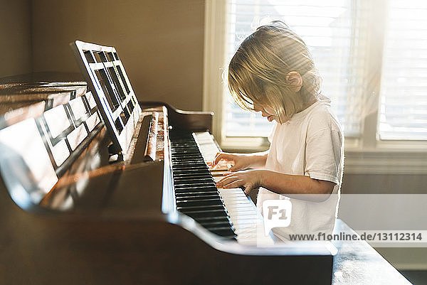 Boy practicing piano at home